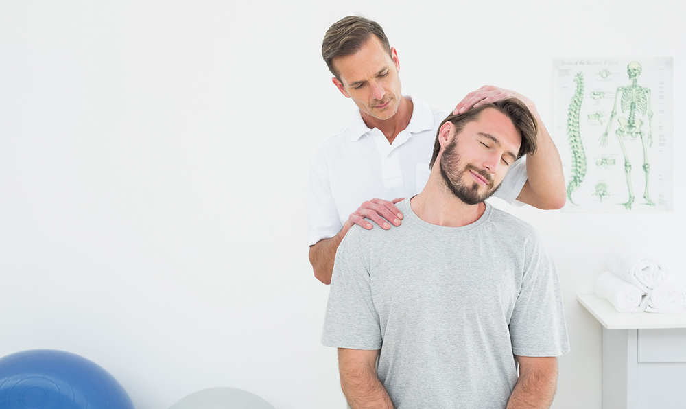 male patient receiving neck pain chiropractic treatment