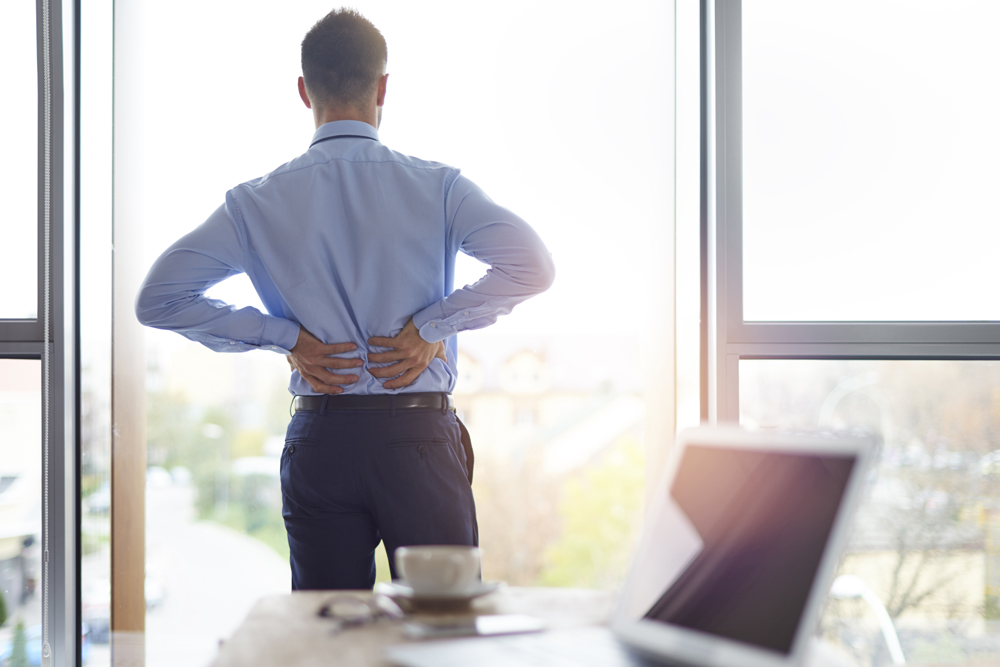 Man with back pain at work needs chiropractic care in Rancho Cucamonga, CA.